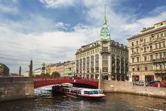 Взгляд красного моста над рекой Moika, торговые дома Esders ? k Skheifals в Санкт-Петербурге стоковые изображения rf