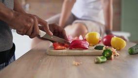 Взгляд крупного плана африканского ` s парня вручает овощи вырезывания подготавливая еду пока его кавказская подруга сидит на видеоматериал