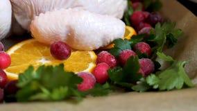 Взгляд крупного плана всего сырцового цыпленка с свежими клюквами петрушки и оранжевыми кусками на олове подноса выпечки подготов Стоковое Фото