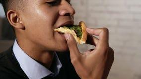 Взгляд крупного плана молодой Афро-американской наслаждаясь пиццы во время обеда на работе Он сдерживает кусок в slowmotion акции видеоматериалы