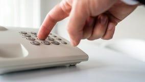Взгляд крупного плана низкого угла мужской руки набирая телефонный номер стоковые изображения
