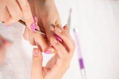 Взгляд крупного плана рук с маникюром обработки ногтя молодой женщины специалистом в салоне стоковое изображение