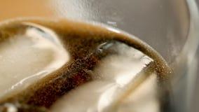 Взгляд крупного плана стекла с темными пить коктеиля и кубов льда в ем делая клокочет стоковая фотография rf