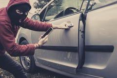 Взгляд крупного плана carjacker пробуя раскрыть автомобиль с выбор-замком Замаскированный человек сидит на корточках и ломает кто стоковое изображение