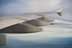 Взгляд крыла самолета во время полета в полдень стоковые фото