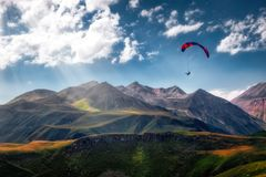 Взгляд ландшафта летания параплана над красивыми горами и небом стоковая фотография rf