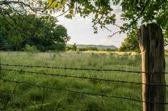 Взгляд луга горы через проволочную изгородь колючки Стоковые Фото