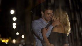 Взгляд любящих пар через брызгая дождевые капли, обнимает и любит, дата стоковое фото rf