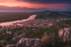 Взгляд малого города с рекой от холма на заходе солнца Стоковая Фотография
