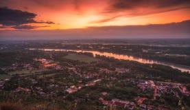 Взгляд малого города с рекой от холма на заходе солнца Стоковое Изображение