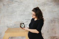 Взгляд матери Beautilul будущий на часах Беременная женщина в костюме черного тела будущая счастливая мать belmont стоковая фотография