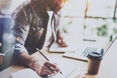 Взгляд молодого бородатого человека держа карандаш и делая тетрадь примечаний Сотрудник на работая процессе горизонтально запачка Стоковая Фотография RF