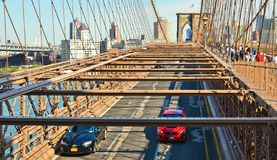 Взгляд на Бруклинском мосте и Гудзоне с автомобилями идущими и современный горизонт в предпосылке в Манхэттене, Нью-Йорке стоковое изображение rf