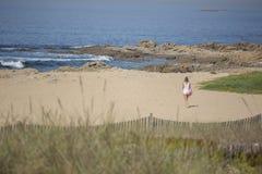 Взгляд на девушке, самостоятельно и идущ на пляж Leca da Palmeira, Португалии стоковые изображения