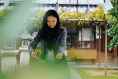 Взгляд на крае горы Schafberg, рук мытья Austriagirl как очищение в виске, Киото, Японии стоковое изображение