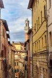 """Взгляд на Torre del Mangia от средневековой узкой улочки через Sant """"Agata Сиена Италия стоковое фото"""