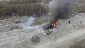 Взгляд неба горя автомобиля в дезертированных полях пыли с двигая motorbikers вокруг сток-видео