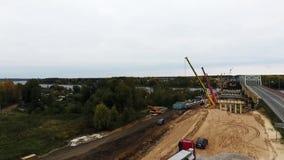 Взгляд неба района строительства моста с 2 кранами близрасположенными проезжей частью и полем акции видеоматериалы