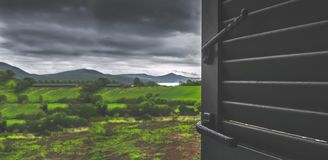 Взгляд неба хмурого дня бурный через сезон дождей дождливых дней дома пребывания окна запачкал предпосылку стоковое фото