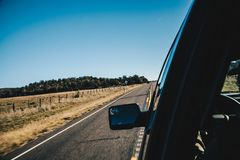Взгляд нерезкости движения дороги с бортовым зеркалом изнутри автомобиля Стоковая Фотография