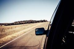 Взгляд нерезкости движения дороги с бортовым зеркалом изнутри автомобиля Стоковые Фотографии RF