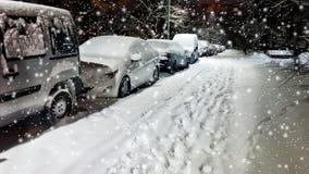 Взгляд низкого угла автомобилей припаркованных вдоль улицы вечером в зиме панорамно стоковые изображения