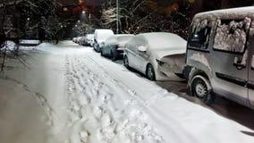 Взгляд низкого угла автомобилей припаркованных вдоль улицы вечером в зиме панорамно стоковое изображение rf