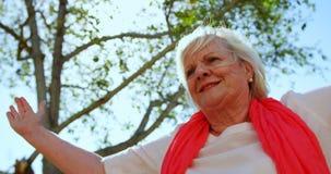Взгляд низкого угла активной кавказской старшей женщины выполняя йогу в саде дома престарелых 4k видеоматериал