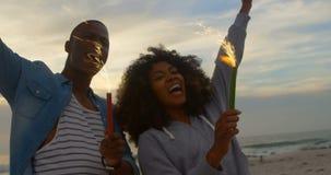 Взгляд низкого угла Афро-американских пар держа бенгальские огни в руке на пляже 4k сток-видео