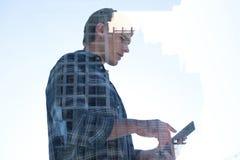 Взгляд низкого угла бизнесмена используя ПК таблетки отражая на окне Стоковое фото RF