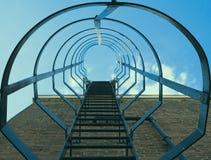 Взгляд низкого угла лестницы клетки безопасности на кирпичной стене против голубого неба с облаками стоковые изображения