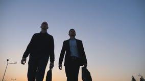 Взгляд низкого угла 2 молодых успешных бизнесменов в официально носке идя с портфелями после работы в вечере акции видеоматериалы