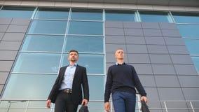 Взгляд низкого угла 2 молодых успешных коллег в официально носке идя с портфелями от офисного здания после работы акции видеоматериалы