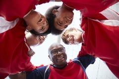 Взгляд низкого угла мужских футболистов и тренера средней школы имея беседу команды стоковое фото rf