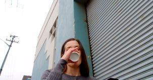 Взгляд низкого угла счастливой женщины используя мобильный телефон в городе 4k акции видеоматериалы
