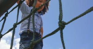 Взгляд низкого угла школьницы смешанн-гонки играя в спортивной площадке школы на солнечный день 4k сток-видео