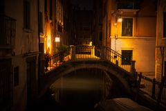 Взгляд ночи Венеции с небольшим мостом в желтом свете фонариков стоковые фото