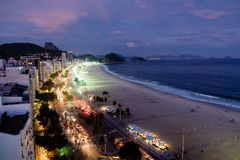 Взгляд ночи пляжа Copacabana во время захода солнца в раннем вечере, принятый от крыши гостиницы, небо фиолетов Рио-де-Жанейро, b Стоковое Изображение RF