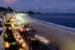 Взгляд ночи пляжа Copacabana во время захода солнца в раннем вечере, принятый от крыши гостиницы, небо фиолетов и ночные жизни Стоковое Изображение