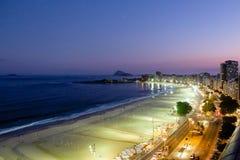 Взгляд ночи пляжа Copacabana во время захода солнца в раннем вечере, принятый от крыши гостиницы, небо фиолетов и ночные жизни Стоковое Фото