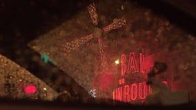 Взгляд ночи румян Moulin через влажное окно автомобиля, Париж акции видеоматериалы