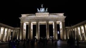 Взгляд ночи строба Бранденбурга в Берлине, людях идет в квадрат, Германию на ноче, Берлин сток-видео