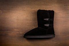 Взгляд одного ботинка зимы на деревянной предпосылке Стоковые Изображения