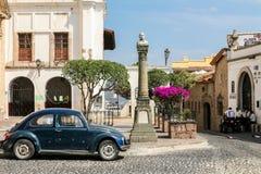 Взгляд одной из центральных улиц с типичным автомобилем жука VW внутри Стоковые Изображения