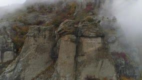 Взгляд около каменного штендера скалы съемка Взгляд сверху каменного штендера утеса с причаливая сильным туманом Ландшафт осени сток-видео