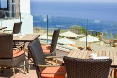 Взгляд открытого кафа в улице против моря с плетеными стульями и деревянными столами в теплой тропической стране стоковое фото