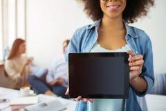 Взгляд отрезка афро американской девушки стоящ и демонстрирующ черная таблетка Ее друзья сидя на таблице Стоковое Фото