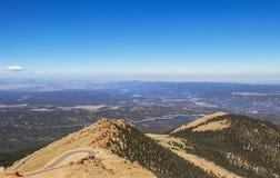 Взгляд от близко верхней части над линией деревьев щук пикового Колорадо дороги кривой hairpin с панорамой в расстоянии включая о стоковое изображение