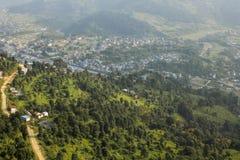 Взгляд от большей высоты к зеленому наклону горы и городу в долине горы на фоне стоковые фото