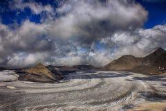 Взгляд от большой высоты на sunlit леднике под красивым облаком Стоковое Изображение